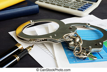 Financial fraud concept. Business documents and handcuffs.