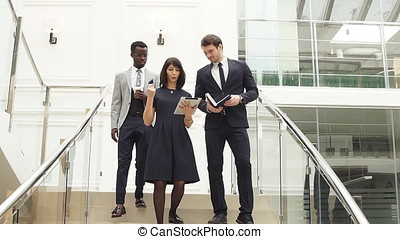 Financial multiethnic team members going down stairs with tablet and smartphone.