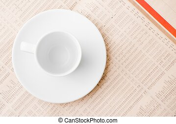 financial newspaper and empty cup of coffee