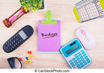 Financial or budget planning concept, top view of notepad with word BUDGET, mobile phone, calculator, and other accessories on wooden background