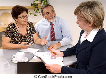 financial planner - Mature couple talking to financial...
