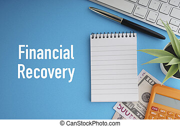 FINANCIAL RECOVERY text with banknotes currencies, fountain pen, notepad, decorative plant, keyboard and calculator on blue background