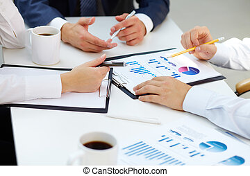 Financial reports - Close-up of business group analyzing...