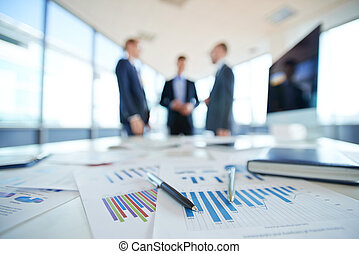 Financial reports - Documents on office table and three men...