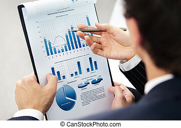 Financial work - Image of human hand pointing at paper...