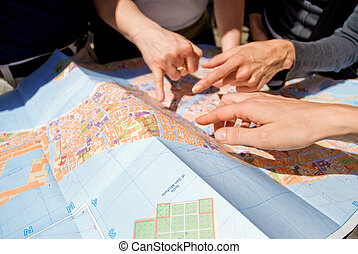 three women hands pointing the destination on the city map