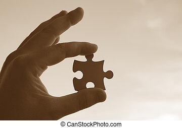 Jigsaw piece on human fingers