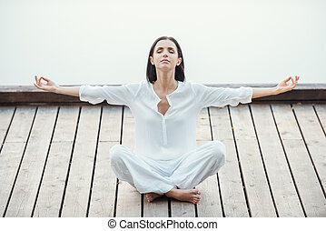 Finding peace and balance. Beautiful young woman in white clothing sitting in lotus position and keeping eyes closed while meditating outdoors