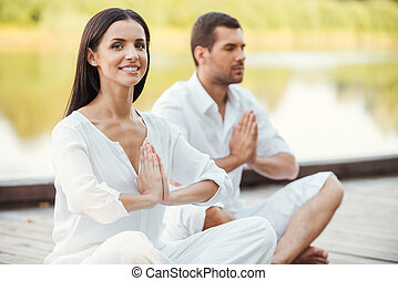 Finding peace and harmony inside themselves. Beautiful young couple in white clothing meditating outdoors together and keeping eyes closed