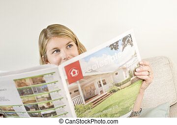 Finding realestate - A blond woman browsing for property in...