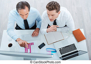 Finding solutions together. Top view of two concentrated business people in formalwear working and looking at computer while sitting at the working place