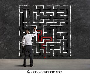 Finding the solution of maze - Businessman finding the...