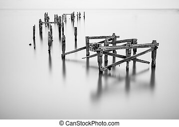 Fine art landscape image of derelict pier in milky long exposure