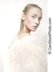 Fine art portrait of a beautiful blonde in white fur