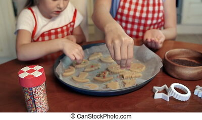 Fine Cuisine - Two girls dusting their handmade biscuits of...