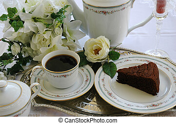 A cup of coffee, a slice of cake, and flowers on a silver tray