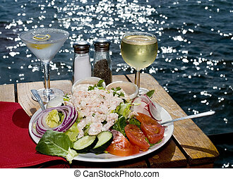 A Seafood Louie and drinks with a water view.