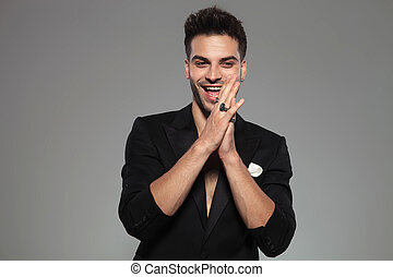 fashion man wearing black tuxedo standing and clapping happy