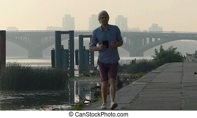 Fine Man in Shorts Turns With His Smartphone. he Goes Along the Dnipro in Slo-Mo