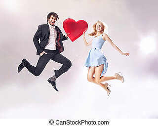 Fine photo of cheerful couple holding a heart