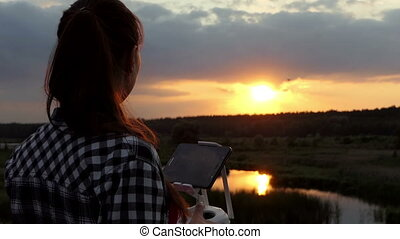 Fine woman works with a panel to control a drone at sunset