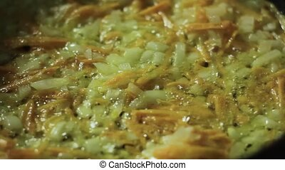 Finely chopped onion fried in a skillet with vegetables.
