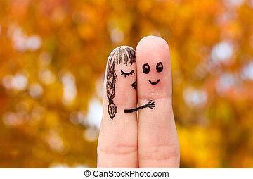 Finger art of a Happy couple. Girl kisses boy on the cheek.