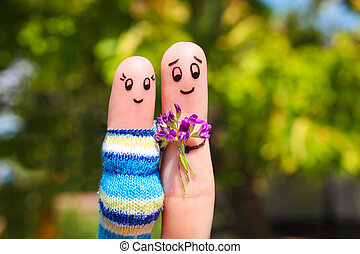 Finger art of a Happy couple. Man is giving flowers pregnant...
