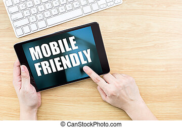 Finger click screen with Mobile friendly word with keyboard on wooden table, Responsive web design.