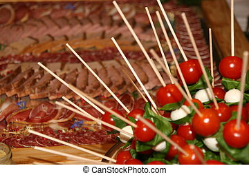 Thies are tomatoes-basil-mozzarella-skewer before a sausage platter.