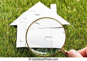 Finger Holding Magnifying Glass Over Puzzle House