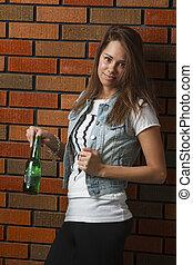 Finger in the bottle - twenty something girl leaning against...