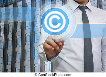 Finger of young businessman point to the blue Copyrighted icon.