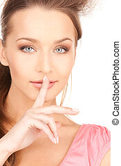 finger on lips - bright picture of young woman with finger...