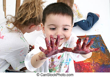 Finger Paint - Adorable toddler boy looking at hands covered...
