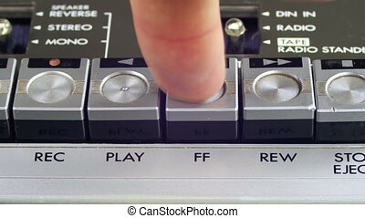 Finger Presses Forward and Rewind Control Buttons on Audio...