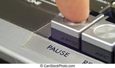 Finger Presses Pause Control Buttons on Audio Cassette...