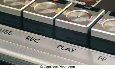 Finger Presses Playback Control Buttons on Audio Cassette Player