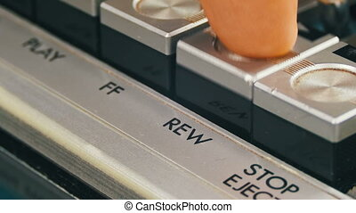 Finger Presses Rewind Control Buttons on Audio Cassette...