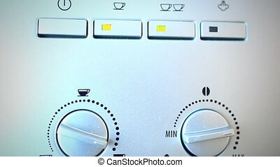 Finger presses the button on the automatic coffee espresso...
