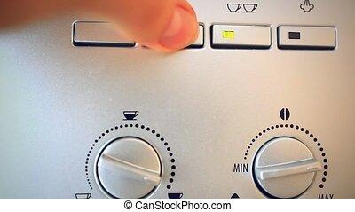 Finger presses the button on the automatic coffee espresso machine.