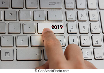 finger pressing keyboard key written 2019 new year on laptop