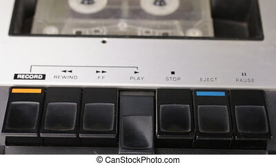 Finger pressing on play, pause button and stop. Retro cassette tape player. Close-up