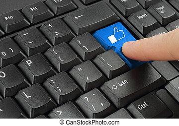 Finger pushing blue social media button on black keyboard