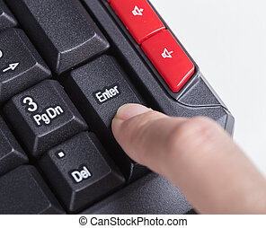 finger pushing enter button on a keyboard
