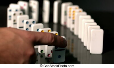 Finger pushing over colourful dominoes in slow motion