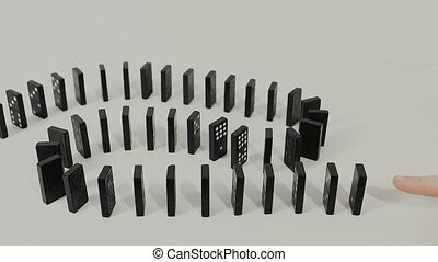 finger toppling dominoes.  Isolated on gray background