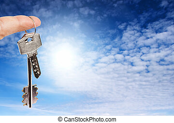 Finger with key on blue sky background