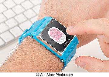 Fingerprint scanning on smartwatch - Man is scanning ...