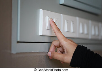 fingers are turning off light switch in the house.
